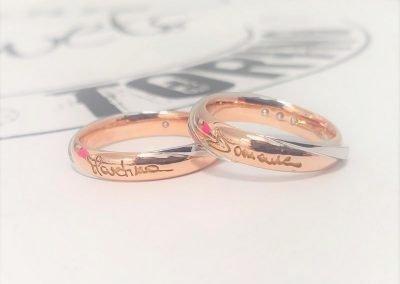 Fedi nuziali bicolore in oro rosa e bianco con firma esterna calligrafica e diamanti interni