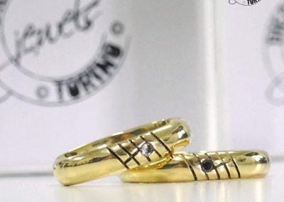 Fedi nuziali classiche in oro giallo con diamante e decoro esterno tema musica