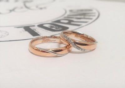 Fedi nuziali in oro rosa con firma interna, baffi in oro bianco e fila diamanti